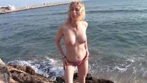 Blonde Aude strips on the rock
