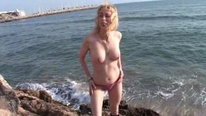 Blonde Aude strips on the rocks