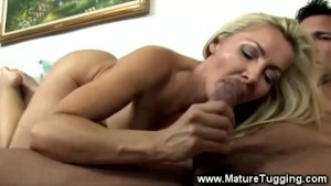 MILF tugs cock while licking the balls