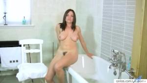 Busty milf fingers herself in the bathroom
