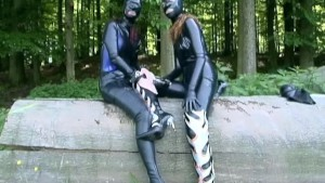 Latex bodysuit girls fooling around outside