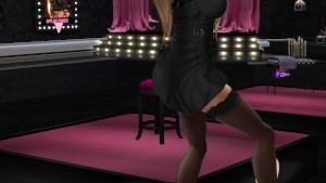 Une jolie femme au cheveux châtains, tatouee en tenue mini robe et bas noire entrain de danser dans un club