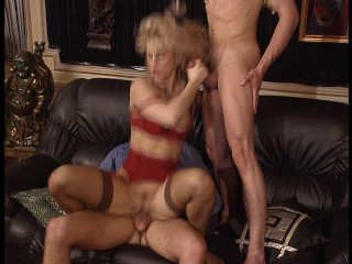 Hot blonde in sexy red lingerie takes on two cocks. (Clip)